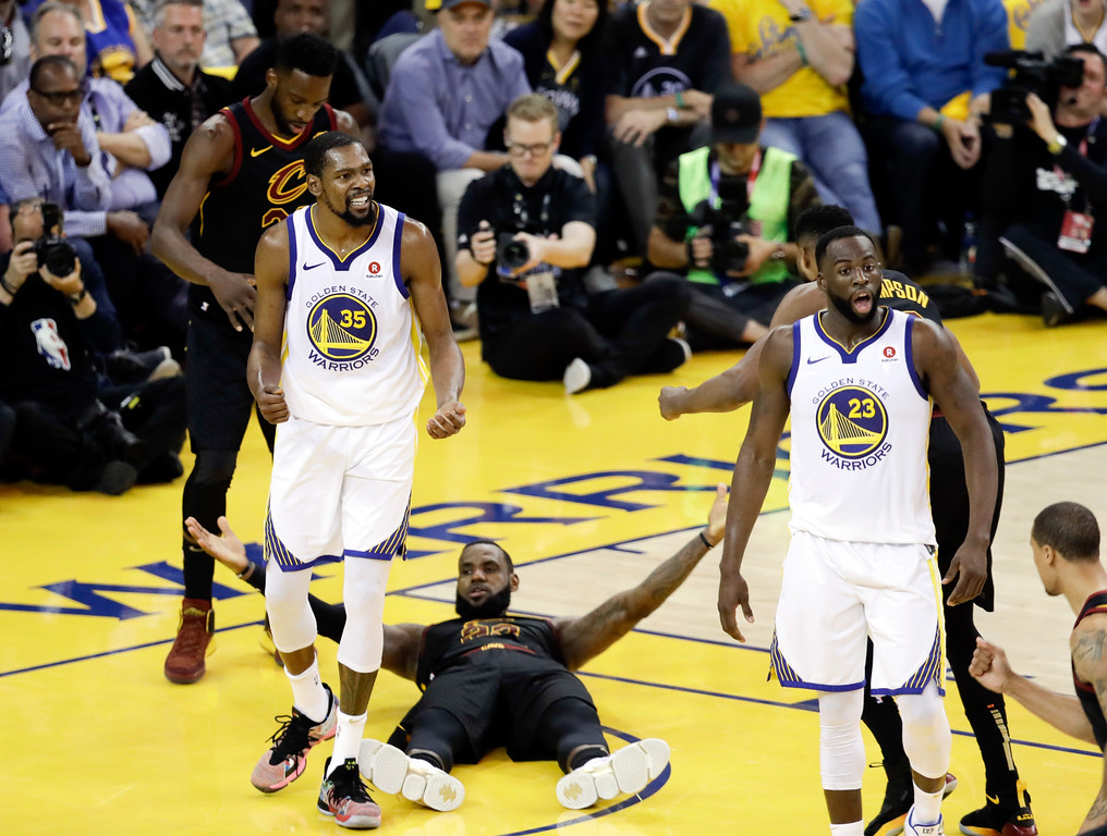 . Golden State Warriors forward Kevin Durant (35) reacts to a call while standing over Cleveland Cavaliers forward LeBron James during the second half of Game 1 of basketball\'s NBA Finals in Oakland, Calif., Thursday, May 31, 2018. (AP Photo/Marcio Jose Sanchez)