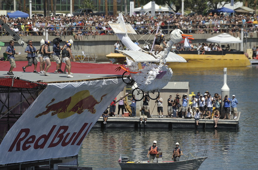 """. LONG BEACH, CALIF. USA -- Brett Hileman pilots \""""Unexpected Delivery\"""" during the Flugtag in Rainbow Harbor in Long Beach, Calif. on August 21, 2010. Thirty five teams competed in the Red Bull event where teams build homemade, human-powered flying machines and pilot them off a 30-foot high deck in hopes of achieving flight.  Flugtag means \""""flying day\"""" in German. They are on distance, creativity and showmanship..Photo by Jeff Gritchen / Long Beach Press-Telegram.."""
