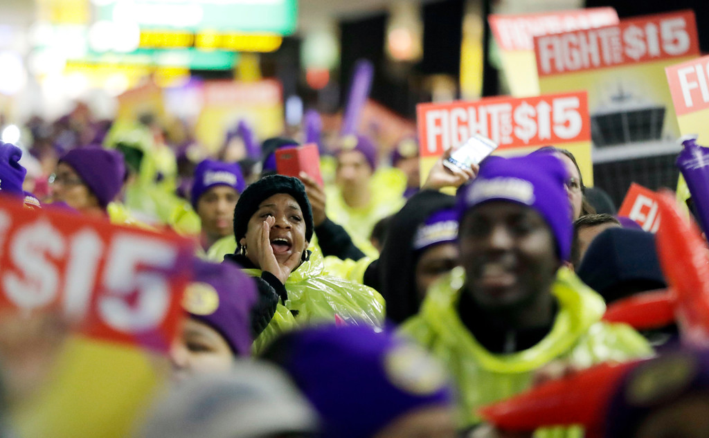 . A woman shouts while marching with service workers asking for $15 minimum wage pay during a rally at Newark Liberty International Airport, Tuesday, Nov. 29, 2016, in Newark, N.J. The event was part of the National Day of Action to Fight for $15. The campaign seeks higher hourly wages, including for workers at fast-food restaurants and airports. (AP Photo/Julio Cortez)