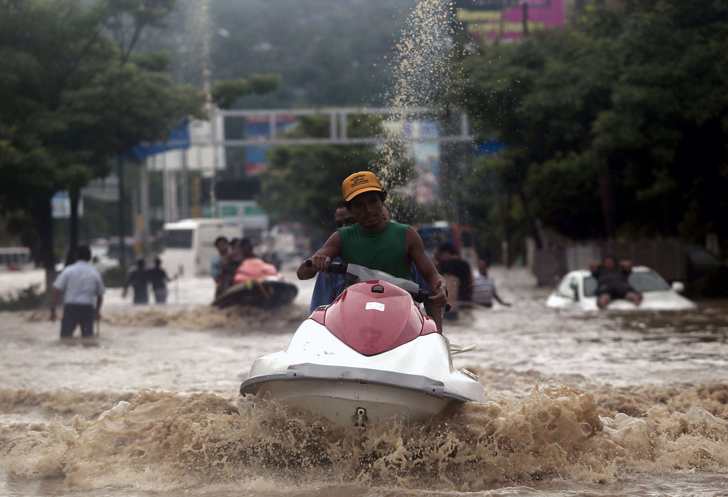 . A man carries residents on a jet ski in Acapulco, Guerrero state, Mexico, after heavy rains hit the area on September 16, 2013. Hurricane Ingrid weakened to tropical storm strength as it made landfall on the northeastern coast in the morning while the Pacific coast was reeling from the remnants of Tropical Storm Manuel, which dissipated after striking on the eve. Thousands of people were evacuated on both sides of the country as the two storms set off landslides and floods that damaged bridges, roads and homes.   Pedro PARDO/AFP/Getty Images