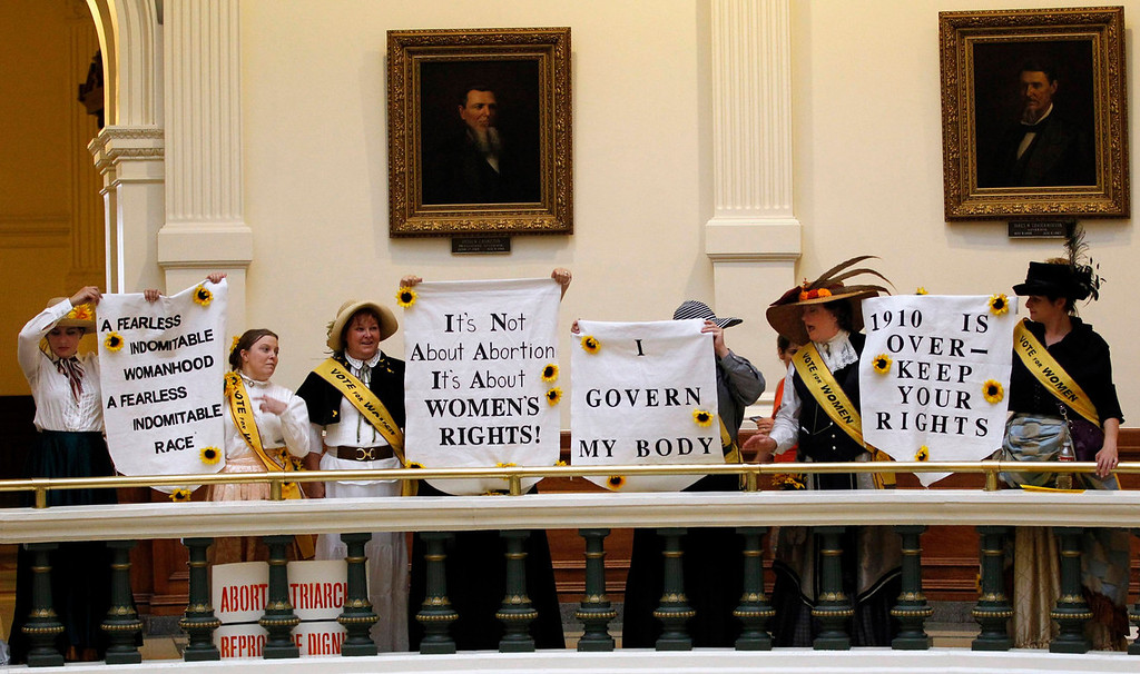 . Protesters hold signs in the rotunda of the State Capitol at a protest before the start of a special session of the Legislature in Austin, Texas July 1, 2013. When the Texas Legislature convenes on Monday for a second special session, the Republican majority will seek to do what it couldn\'t pull off in the first: Pass sweeping abortion restrictions.  REUTERS/Mike Stone