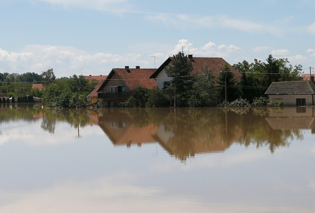. Houses reflected in a flooded area in Obrenovac, some 30 kilometers (18 miles) southwest of Belgrade, Serbia, Monday, May 19, 2014. Belgrade braced for a river surge Monday that threatened to inundate Serbia\'s main power plant and cause major power cuts in the crisis-stricken country as the Balkans struggle with the consequences of the worst flooding in southeastern Europe in more than a century. (AP Photo/Darko Vojinovic)