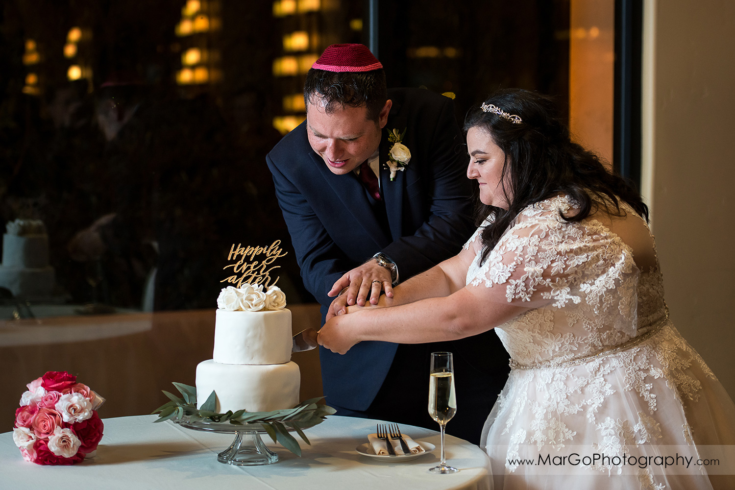 jewish bride and groom cutting cake during wedding reception at Livermore Garre Vineyard and Winery
