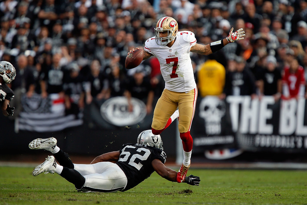 . OAKLAND, CA - DECEMBER 07:  Colin Kaepernick #7 of the San Francisco 49ers avoids the sack from Khalil Mack #52 of the Oakland Raiders in the second quarter at O.co Coliseum on December 7, 2014 in Oakland, California.  (Photo by Brian Bahr/Getty Images)