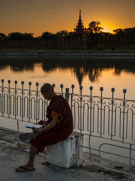 The area around the palace is a popular place at sunset. Here a monk enjoys a peaceful moment to read a book.  Mandalay, 2017