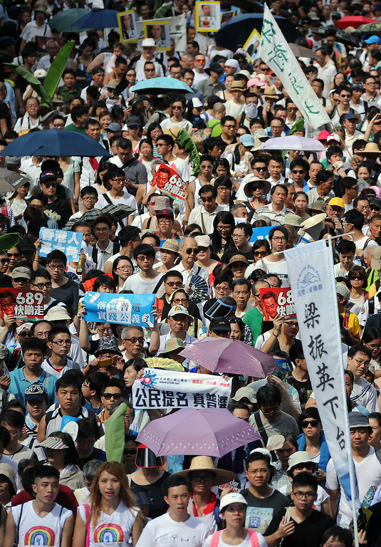 ". Protesters march during a pro-democracy rally seeking greater democracy in Hong Kong on July 1, 2014 as frustration grows over the influence of Beijing on the city. July 1 is traditionally a day of protest in Hong Kong and also marks the anniversary of the handover from Britain to China in 1997, under a ""one country, two systems\"" agreement.   DALE de la REY/AFP/Getty Images"