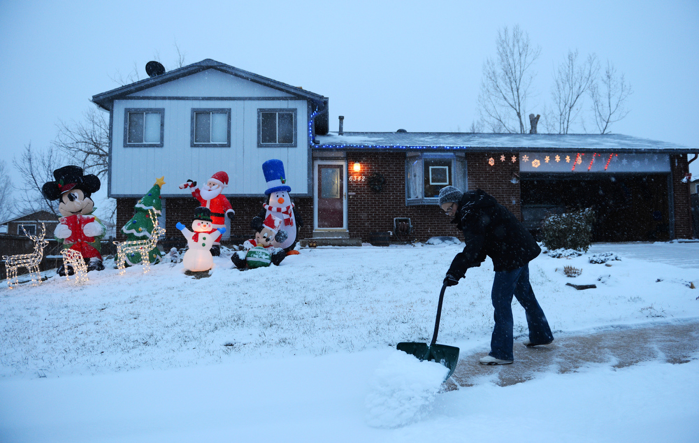 . It\'s starting to look like Christmas outside Amber Bilby\'s home in Arvada, Tuesday, December 18, 2012, as she shovels the walkways. Snow continues to falls though out much of the metro area.  RJ Sangosti, The Denver Post
