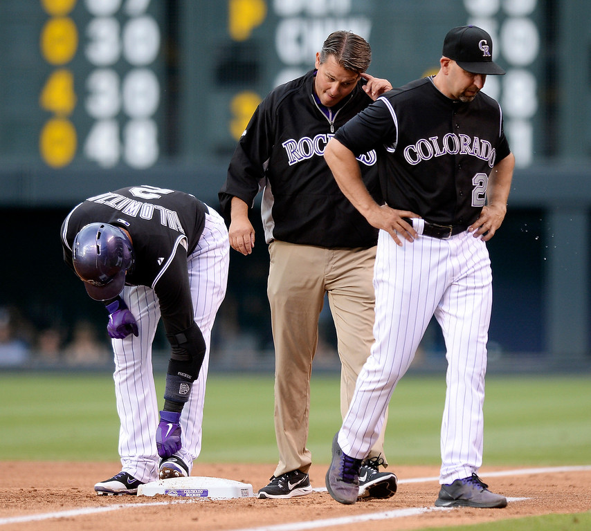 . Colorado Rockies trainer Keith Dugger and manager Walt Weiss walked back to the dugout after checking on Troy Tulowitzki who was hit by a pitch in the first inning. The Colorado Rockies hosted the Atlanta Braves Tuesday night, June 10, 2014. (Photo by Karl Gehring/The Denver Post)