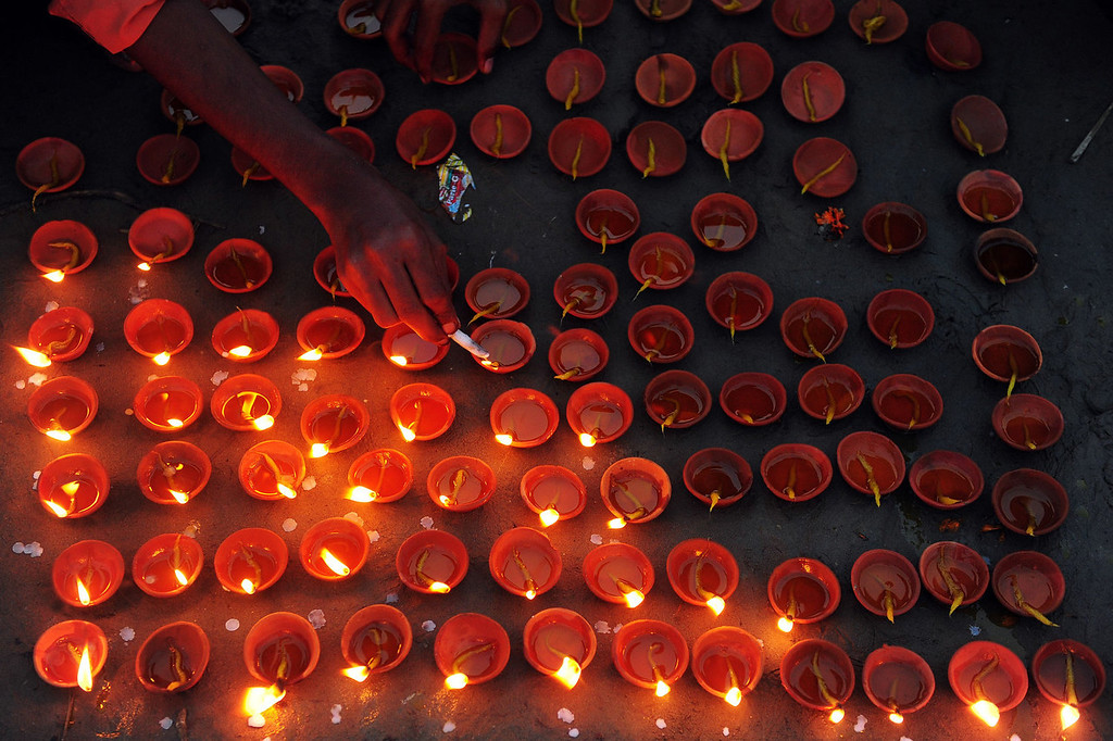 . An Indian reveler lights earthen lamps during Diwali celebrations in Allahabad on November 3, 2013. Diwali marks the homecoming of the Hindu god Lord Ram after vanquishing the demon king Ravana and symbolizes taking people from darkness to light and the victory of good over evil.  Sanjay Kanojia/AFP/Getty Images