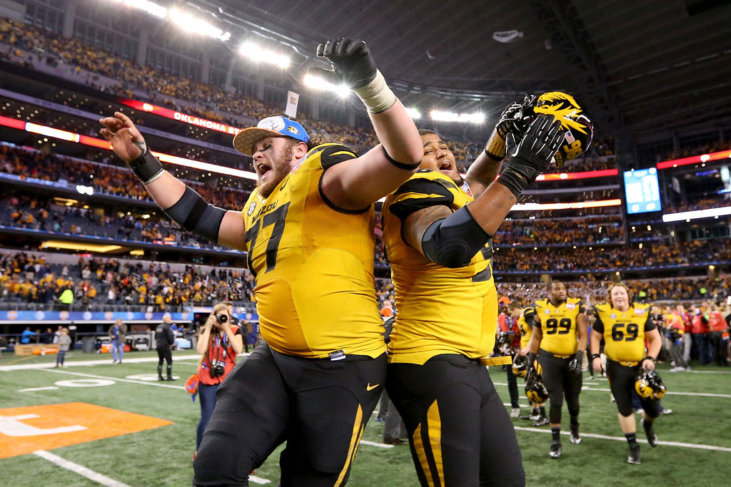 . ARLINGTON, TX - JANUARY 03:  Evan Boehm #77 and Lucas Vincent #96 of the Missouri Tigers celebrates the Tigers 41-31 victory against the Oklahoma State Cowboys during the AT&T Cotton Bowl on January 3, 2014 in Arlington, Texas.  (Photo by Ronald Martinez/Getty Images)