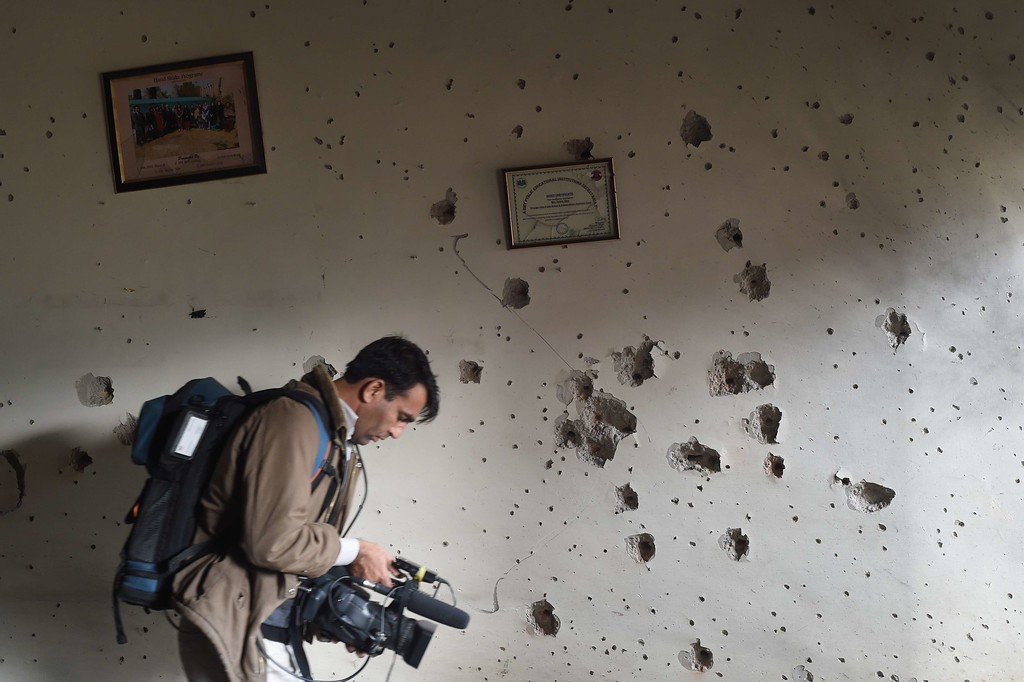 . A Pakistani camera man shoots video in front of a bullet-riddled wall at the arm- run school a day after an attack by Taliban militants in Peshawar on December 17, 2014.   Pakistan mourned 148 people - mostly children - killed by the Taliban in a school massacre that prompted global revulsion and put the government under new pressure to combat the scourge of militancy.   AFP PHOTO / Farooq  NAEEM/AFP/Getty Images