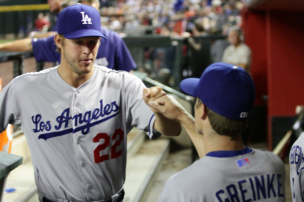 . Clayton Kershaw #22 and Zach Greinke #21 of the Los Angeles Dodgers fist bump in the sixth inning against the Arizona Diamondbacks at Chase Field on April 12, 2014 in Phoenix, Arizona.  (Photo by Jason Wise/Getty Images)