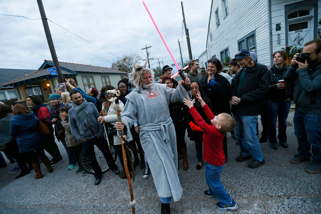 ". Wade Heaton, dressed in costume, entertains a child with a light saber during a parade in honor of actress Carrie Fisher, who played Princess Leia in the ""Star Wars\"" movie series, in New Orleans, Friday, Dec. 30, 2016. Fisher died at on Dec. 27, 2016, at the age of 60. The parade was held by the Krewe of Chewbacchus, a \""Star Wars\"" themed Mardi Gras Krewe. (AP Photo/Gerald Herbert)"