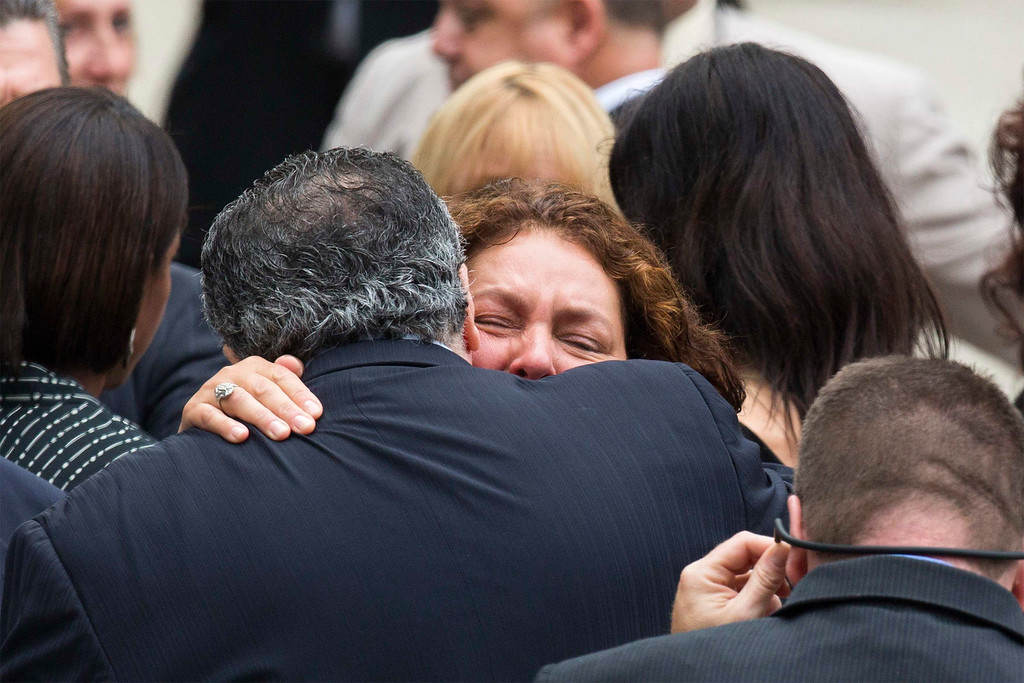 . Actress Aida Turturro embraces a fellow mourner as she arrives for the funeral services of James Gandolfini outside the Cathedral Church of Saint John the Divine in New York June 27, 2013.  REUTERS/Lucas Jackson