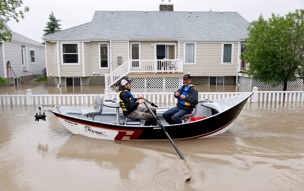 . Two men use a fishing boat to rescue residents from a neighborhood after heavy rains caused flooding, closed roads, and forced evacuation in High River, Alta., Thursday, June 20, 2013. Calgary city officials say as many as 100,000 people could be forced from their homes due to heavy flooding in western Canada, while mudslides have forced the closure of the Trans-Canada Highway around the mountain resort towns of Banff and Canmore. (AP Photo/The Canadian Press, Jeff McIntosh )