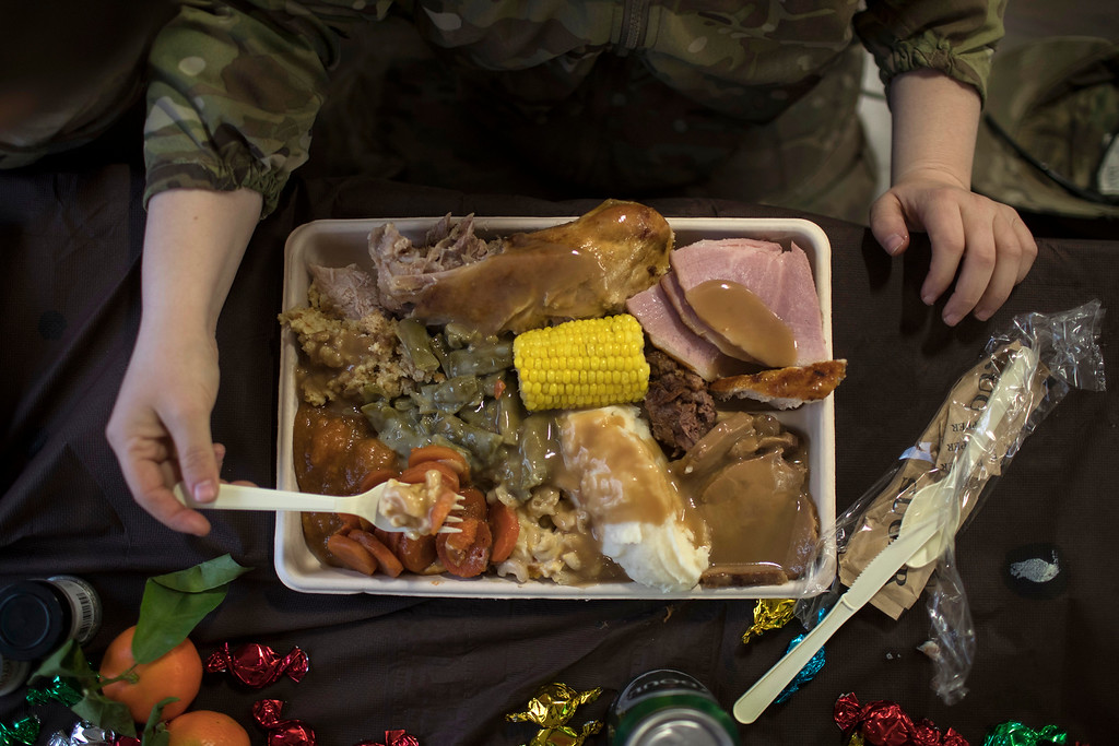 . An U.S. Army soldier eats Thanksgiving dinner at a coalition air base in Qayara south of Mosul, Iraq, Thursday, Nov. 24, 2016. (AP Photo/Felipe Dana)
