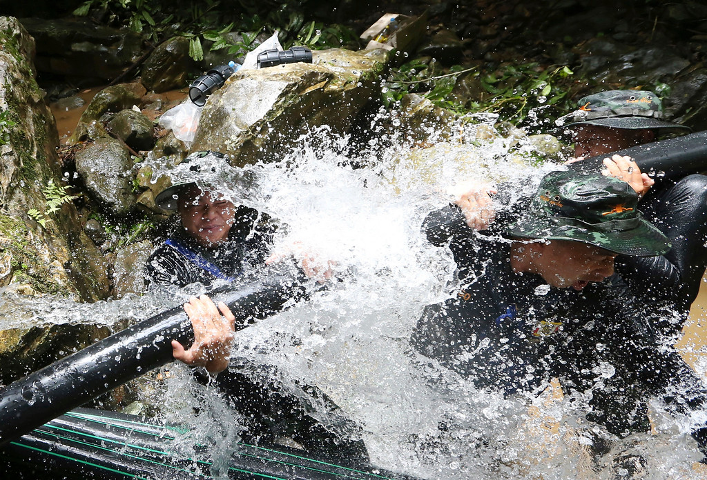. Thai soldiers try to connect water pipes that will help bypass water from entering a cave where 12 boys and their soccer coach have been trapped since June 23, in Mae Sai, Chiang Rai province, in northern Thailand Saturday, July 7, 2018. Thai authorities are racing to pump out water from the flooded cave before more rains are forecast to hit the northern region. (AP Photo/Sakchai Lalit)