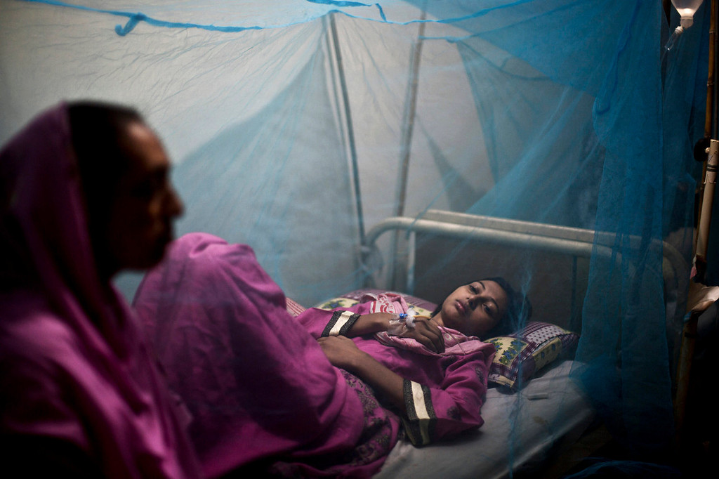 . A Pakistani woman, looks after her daughter suffering from the mosquito-borne disease, dengue fever, while laying in bed covered with a net at an isolation ward of a hospital in Rawalpindi, Pakistan, Thursday, Oct. 24, 2013. Dengue, a flu-like illness, is spread by the Aedes mosquito and spikes during the annual monsoons in Pakistan, when the rains leave puddles of stagnant water where the insects breed. (AP Photo/Muhammed Muheisen)