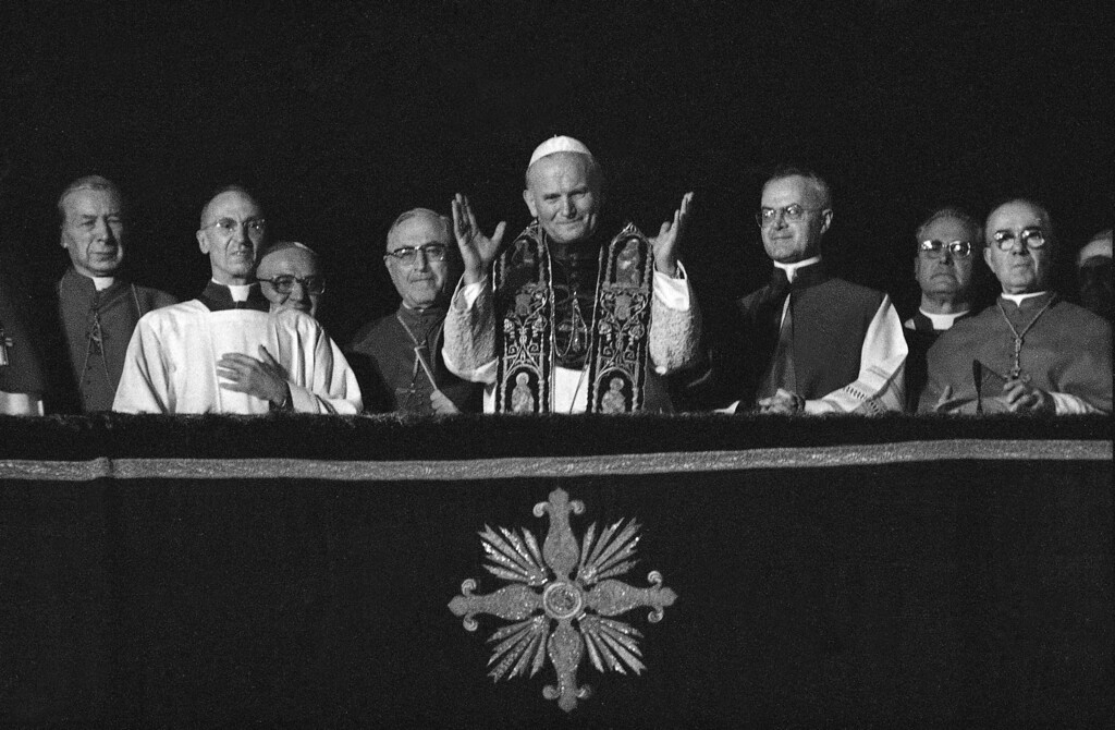 . Pope John Paul II greets the cheering crowd from the balcony of St. Peter\'s Basilica in Vatican City, Monday evening, Oct. 16, 1978, shortly after his election to succeed the late Pope John Paul I, Oct. 16, 1978.  The new head of the Catholic Church, the former archbishop of Krakow, Poland, Karol Cardinal Wojtyla, is the first non-Italian since 450 years. The pontiff is flanked by, from left to right, Polish Cardinal Stefan Wyszynski; Msgr. Orazio Cocchetti of the pontifical ceremonies office; cardinal Bertoli of Italy; cardinal Siri of Italy; and Msgr. Virgilio Noe of the pontifical cermonies office.  (AP Photo)
