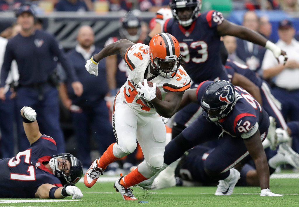 . Cleveland Browns running back Isaiah Crowell (34) runs the ball evading tackle attempts by Houston Texans linebacker Brennan Scarlett (57) and defensive end Brandon Dunn (92) in the first half of an NFL football game, Sunday, Oct. 15, 2017, in Houston. (AP Photo/Eric Gay)