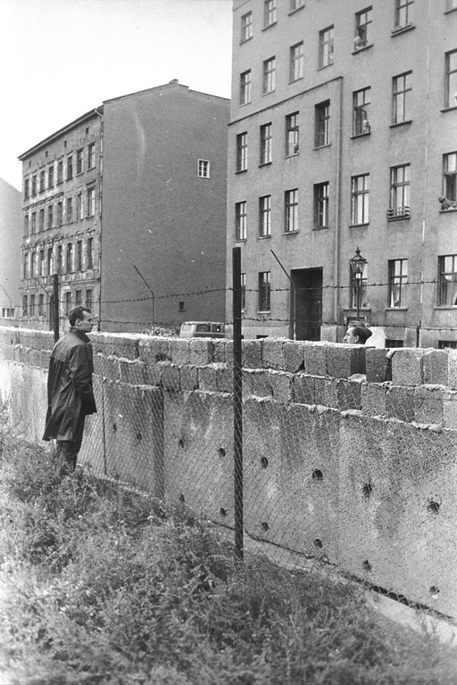 . A citizen of East Berlin peers through barbed wire at a West Berliner over the Berlin Wall , Berlin, Germany, 1960s. The mass immigration of Germans from Communist Berlin to Western Berlin inspired East Germany military leader Erich Honeker to construct  the blockade,  a barricade of concrete walls, mine fields and guard posts that stretched for 100 miles. (Photo by Hulton Archive/Getty Images)