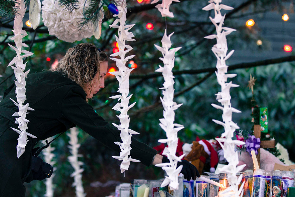 ". A woman lights candles while visiting a memorial to the victims of the recent shooting in Sandy Hook Village in Newtown, Connecticut, December 17, 2012. The small Connecticut town shattered by an act President Barack Obama  called ""unconscionable evil,\"" holds on Monday the first two of 20  funerals for schoolchildren massacred in their classrooms last week.  REUTERS/Lucas Jackson"
