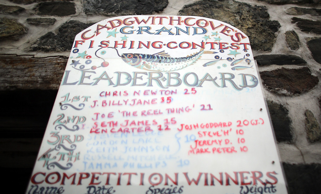 . CADGWITH, ENGLAND - SEPTEMBER 05: The Cadgwith Cove\'s Fishing Contest leaderboard is displayed prior to the final fortnightly fishing competition of the year in Cadgwith on September 5, 2013 in Cornwall, England. The summertime competition to catch the heaviest fish of a chosen type, (for this final the fish was bass) allows locals and visitors the chance to fish for fun and a cash prize, with the catch cooked in a pot at the end of the night on some occasions. Set on the Lizard peninsula in Cornwall, the village of Cadgwith, which was established in medieval times, owes its existence to the fishing industry. However, whilst fishing remains an important part of village life today, tourism is also now a major source of income for the inhabitants. (Photo by Matt Cardy/Getty Images)