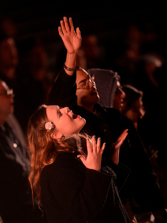 . Lucy Rosta, 18, left, and Willard Hughs, right, both of Highland, sing a worship song during Easter Sunrise services at the Roosevelt Bowl in San Bernardino March 31, 2013.  Over 600 local Christians gathered to celebrate the resurrection of Jesus Christ.  GABRIEL LUIS ACOSTA/STAFF PHOTOGRAPHER.
