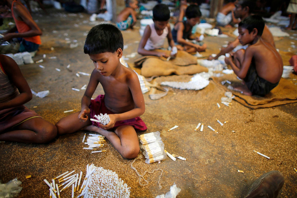 """. Children fill up empty cigarettes manually with locally grown tobacco in a small bidi (cigarette) factory at Haragach in Rangpur district, Bangladesh July 11, 2013. According to a 2012 study by US-based NGO, Campaign for Tobacco-Free Kids, over 45,000 people in Bangladesh are employed in manufacturing inexpensive cigarettes known as bidis and this number includes \""""many women and children working in household based establishments where they make low wages and live in poverty.\"""" A 2011 research paper about bidi workers in Bangladesh, published in the journal Tobacco Control, says that working conditions can involve poor ventilation and exposure to tobacco dust, which can cause a range of health problems including respiratory and skin diseases. International attention has been focused on workers\' safety in Bangladesh since the disaster at Rana Plaza, a garment factory complex which collapsed in April, killing 1,132 workers.  REUTERS/Andrew Biraj"""