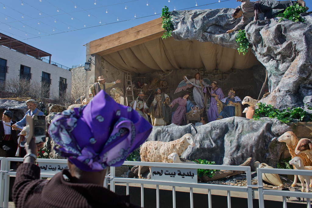 . A tourist takes a picture of the Nativity scene that is set at the Manger Square, by the Church of the Nativity, traditionally believed by Christians to be the birthplace of Jesus Christ, ahead of Christmas, in the West Bank city of Bethlehem, Sunday, Dec. 17, 2017. (AP Photo/Nasser Nasser)