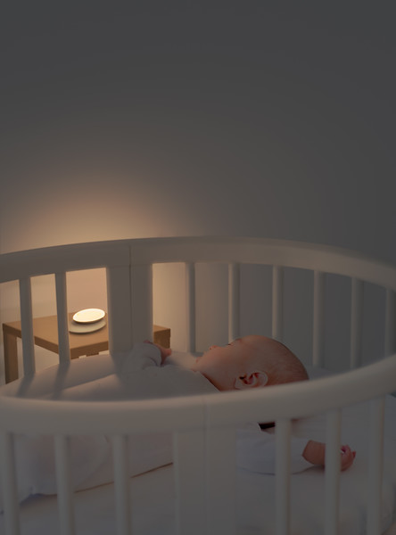 Portrait of a newborn baby boy sleeping in a white round crib with canopy