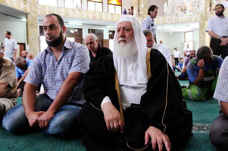 """. Prominent conservative cleric Da\'i al-Islam al-Shahhal (R) sits in a mosque during Friday prayers in Tripoli, northern Lebanon June 7, 2013. Sunni Muslim preachers condemned Iran and its \""""Satanic\"""" Shi\'ite allies in Friday sermons, after a battle in Syria that has inflamed sectarian rhetoric which risks spreading violence around the Middle East. Shahhal urged followers to resist Iranian attempts to control Iraq, Lebanon and Syria as a step to conquering the Gulf states. REUTERS/Omar Ibrahim"""