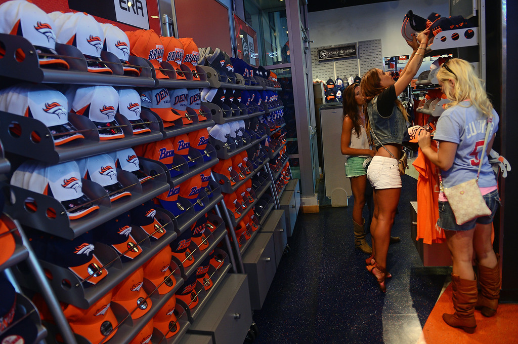 . Kerri Stern stands on her tippy toes to reach a Broncos hat to try on with her friends Danielle Glucky, right, and Toni Damico at the Denver Broncos Team store at of Sports Authority Field at Mile High. Glucky and Stern came all the way from Minneapolis, Minnesota to attend the football game.  Photo by Helen H. Richardson/The Denver Post