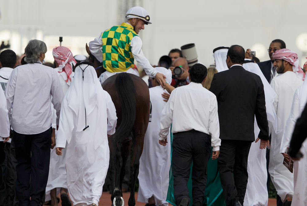 . Olivier Peslier of France riding on Rabbah De Carrere celebrates after he wins the Kahayla Classic, a race held during the Dubai World Cup horse races at Meydan Racecourse in Dubai, United Arab Emirates, Saturday, March 29, 2014. (AP Photo/Kamran Jebreili)