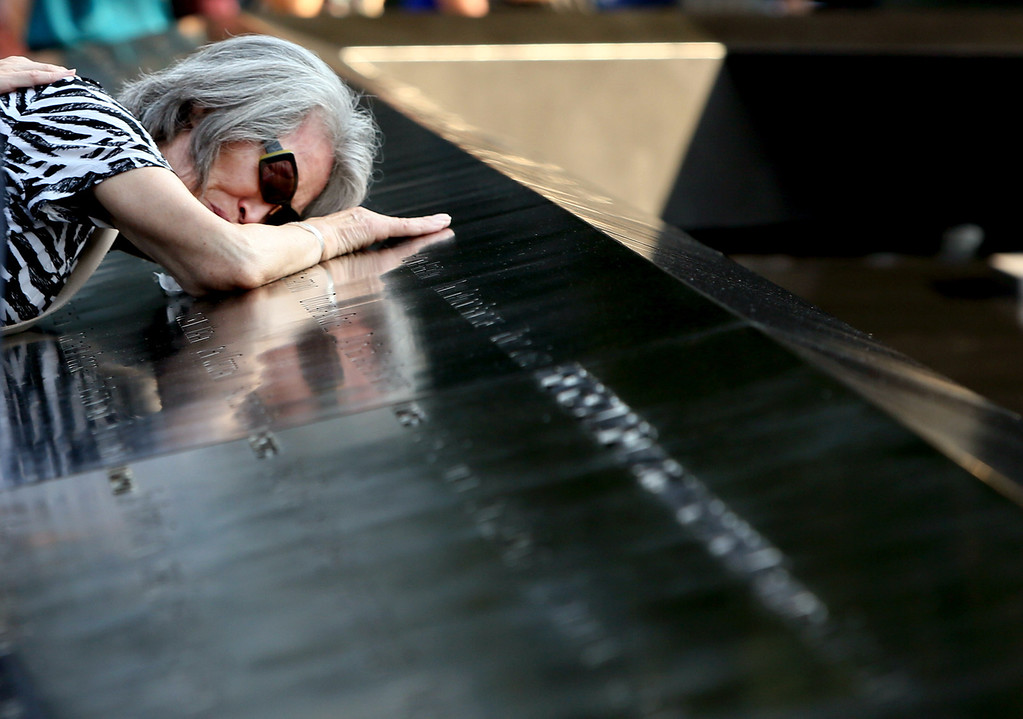 . Mija Quigley of Princeton Junction, NJ embraces the name of her son Patrick Quigley who died aboard Flight 175 during ceremonies for the twelfth anniversary of the terrorist attacks on lower Manhattan at the World Trade Center site on September 11, 2013 in New York City. The nation is commemorating the anniversary of the 2001 attacks which resulted in the deaths of nearly 3,000 people after two hijacked planes crashed into the World Trade Center, one into the Pentagon in Arlington, Virginia and one crash landed in Shanksville, Pennsylvania. Following the attacks in New York, the former location of the Twin Towers has been turned into the National September 11 Memorial & Museum.  (Photo by Chris Pedota-Pool/Getty Images)