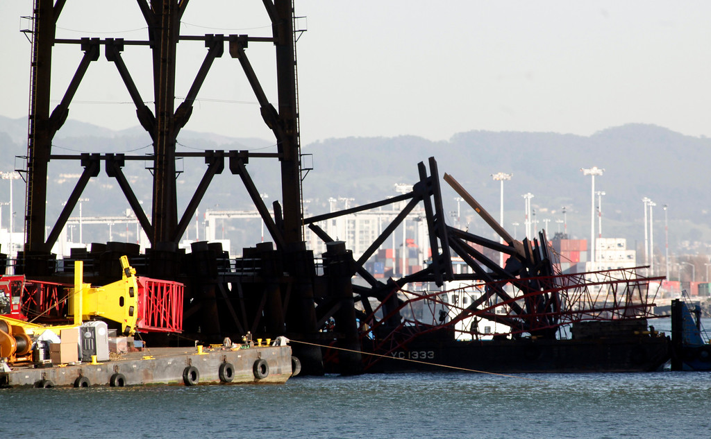 . A section of iron falsework that still tangled with a section of crane boom is pushed away from the new Bay Bridge project after an accident near Treasure Island on Thursday, Feb. 21, 2013 in San Francisco. (Karl Mondon/Staff)