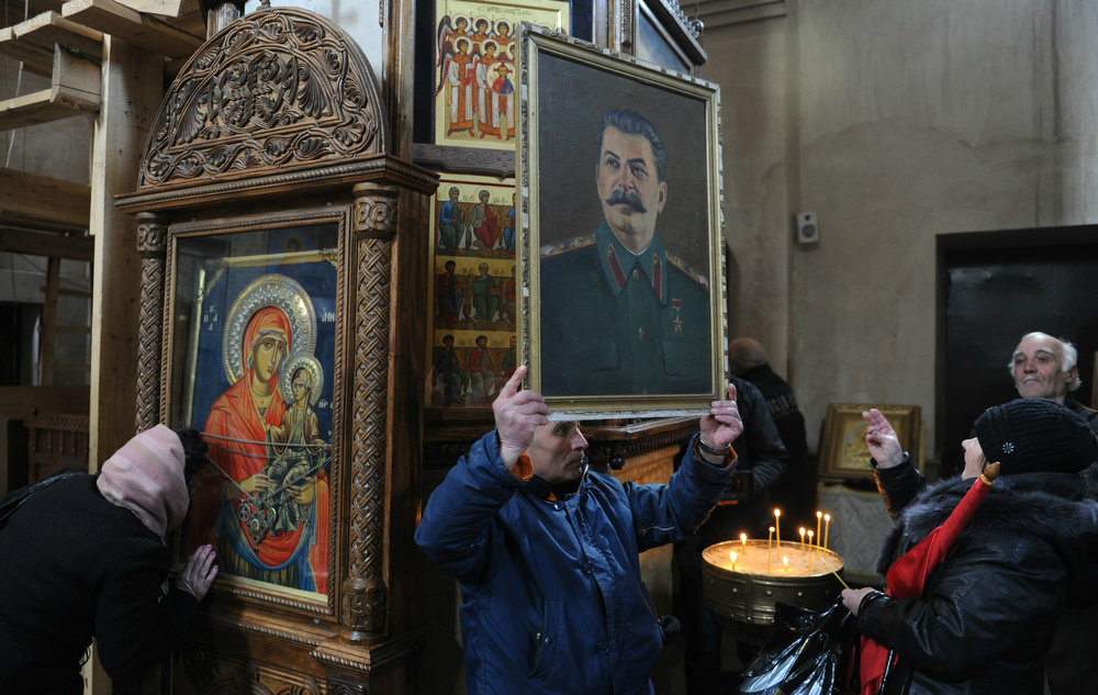 . A man holds a portrait of Soviet dictator Joseph Stalin inside a church in Stalin\'s native town of Gori, some 50 miles from the capital on March 5, 2013, during ceremonies to mark the 60th anniversary of Stalin\'s death. VANO SHLAMOV/AFP/Getty Images