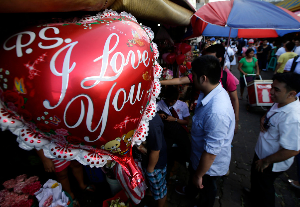 . Filipinos flock to the flower street called Dangwa to buy flowers for their loved ones in celebration of Valentine\'s Day Thursday Feb. 14, 2013 in Manila, Philippines. Business is brisk at this flower street and flower shops around Manila with red roses being the most popular among the buyers. (AP Photo/Bullit Marquez)