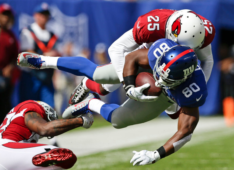 . Arizona Cardinals cornerback Jerraud Powers (25) tackles New York Giants wide receiver Victor Cruz (80) during the first half of an NFL football game Sunday, Sept. 14, 2014, in East Rutherford, N.J.  (AP Photo/Kathy Willens)