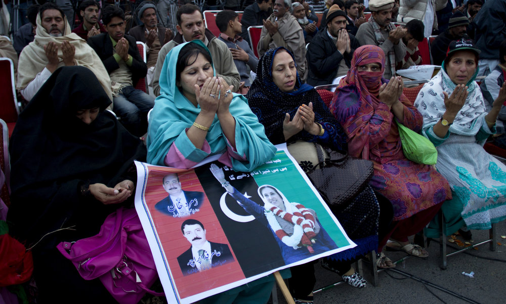 Description of . Supporters of Pakistan's assassinated leader Benazir Bhutto pray during her fifth death anniversary in Rawalpindi, Pakistan, Thursday, Dec. 27, 2012. The 24-year-old son of former Pakistani Prime Minister Benazir Bhutto has launched his political career at his ancestral place Larkana, with a fiery speech on the fifth anniversary of his mother's assassination. (AP Photo/B.K. Bangash)