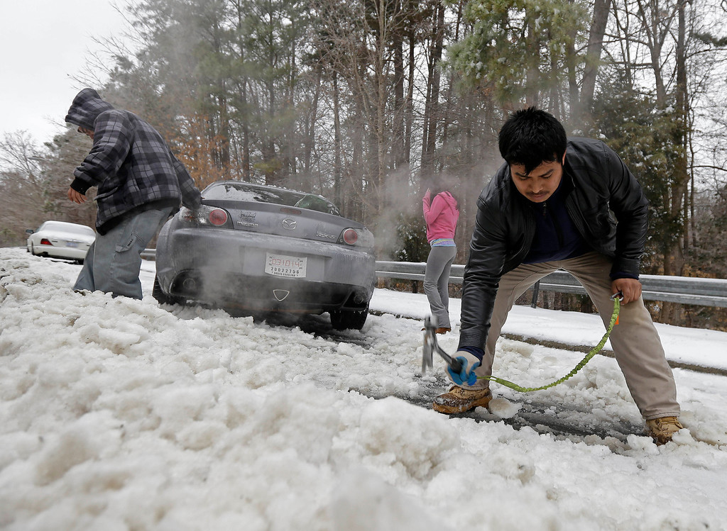 . Passerby Leo Cruz, left, helps Julian Ramirez, right, dig Ramirez\'s car from the frozen roadside after abandoning the car overnight during the storm in Chapel Hill, N.C., Thursday, Feb. 13, 2014. The National Weather Service issued a winter storm warning lasting into Thursday covering 95 of the state\'s 100 counties. (AP Photo/Gerry Broome)