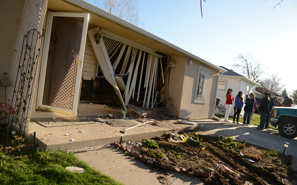 . Family and friends wait for Denver Fire to shore up the walls in a home where a car crash into a house, at the 5100 block of Gill Place in Denver, April 04, 2013. No one was hurt inside the home. (Photo By RJ Sangosti/The Denver Post)