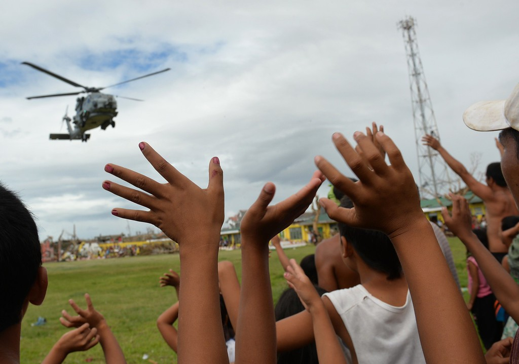 . Residents wave to a US navy seahawk helicopter which dropped off relief goods in the town of Giporlos, Eastern Samar province, central Philippines on November 16, 2013. Spearheaded by a US aircraft carrier group, foreign relief efforts have stepped up a gear in the storm-devastated Philippines eight days after Super Typhoon Haiyan left thousands dead and millions homeless. AFP PHOTO/TED ALJIBE/AFP/Getty Images