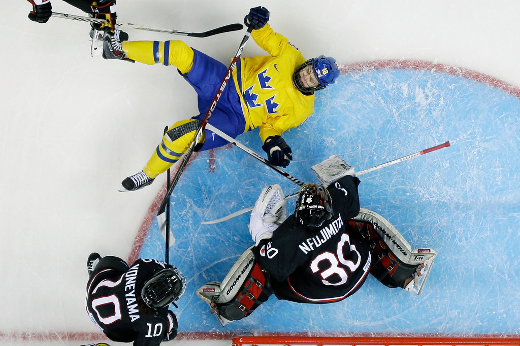 . Anna Borgqvist of Sweden slides on her back past Haruna Yoneyama and Goalkeeper Nana Fujimoto of Japan during the second period of 2014 Winter Olympics women\'s ice hockey game at Shayba Arena, Sunday, Feb. 9, 2014, in Sochi, Russia. (AP Photo/Matt Slocum )