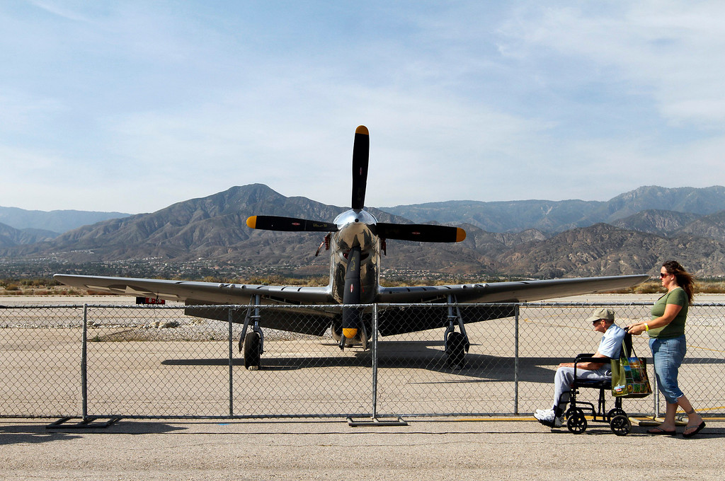 . Diane Hurtado, 47, right, wheels her grandfather Frank Robison, 95, of Redlands, to a stop in front of a P-51 Mustang at the Hangar 24 AirFest and 6th Anniversary Celebration on Friday, May 16, 2014 at the Redlands Municipal Airport in Redlands, Ca. Hurtado says Robison served in World War II and flew 87 missions in a P-51 which is the plane they specifically visited the AirFest to see. (Photo by Micah Escamilla/Redlands Daily Facts)