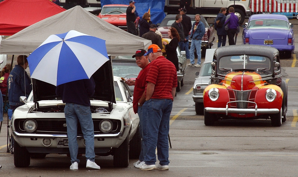 . Spectators checkout classic Camero on display in the parking lot of the Phoneix Plaza in downtown Pontiac during Friday night\'s Woodward Dream Cruise. The annual classic cruise goes from Pontiac to Ferndale covering 16-miles of classic cars, food & entertainment along the way.