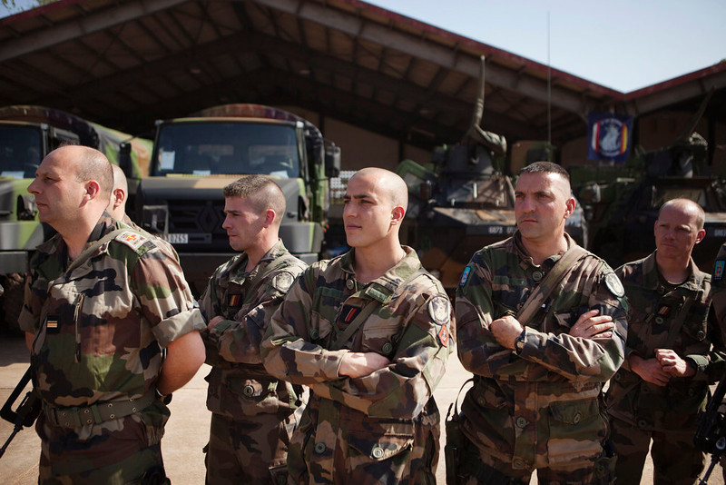 . French soldiers listen as Malian President Dioncounda Traore speaks at a Malian air base in Bamako, Mali January 16, 2013. French troops launched their first ground assault against Islamist rebels in Mali on Wednesday in a broadening of their operation against battle-hardened al Qaeda-linked fighters who have resisted six days of air strikes. REUTERS/Joe Penney