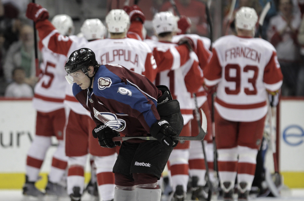. Colorado Avalanche center Matt Duchene (9) skates past the Detroit Red Wings as they celebrate Pavel Datsyuk\'s game-winning goal in overtime of an NHL hockey game Friday, April 5, 2013, in Denver. Detroit won 3-2. (AP Photo/Joe Mahoney)