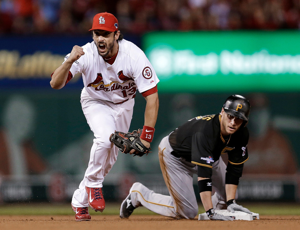 . St. Louis Cardinals second baseman Matt Carpenter, left, celebrates after turning a double play as Pittsburgh Pirates\' Clint Barmes, right, watches the play at first base that ended the top of the sixth inning in Game 5 of a National League baseball division series, Wednesday, Oct. 9, 2013, in St. Louis. Starling Marte hit into the double play. (AP Photo/Jeff Roberson)