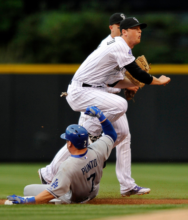 . Los Angeles Dodgers\' Nick Punto (7) is forced out at second by Colorado Rockies second baseman DJ LeMahieu (9), who watches his throw to first during the first inning of a baseball game, Tuesday, Sept. 3, 2013, in Denver. Michael Young was out at first to complete the double play. (AP Photo/Jack Dempsey)